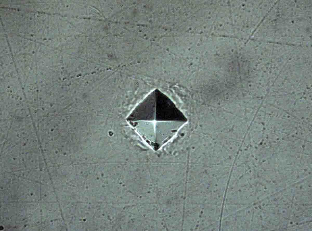 This is a fully-lit indent in a brass sample to illustrate the pyramid shape of the indenter, magnified 500 times.