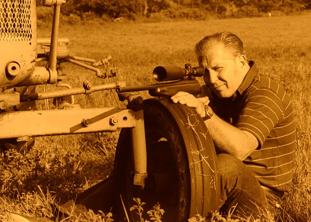 Stan is shown in the field with his rifle. The photo has been tinted to give it the look of a black and white print.